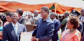 President Edgar Lungu presents a certificate to lowrance Matimero of Barclays Bank for the Most Honest worker award during 2017 Labour Day Celebration at Freedom Statue whilst Minister Labour of Joyce Simukoko looks on yesterday 01-05-2017. Picture by ROYD SIBAJENE/ZANIS