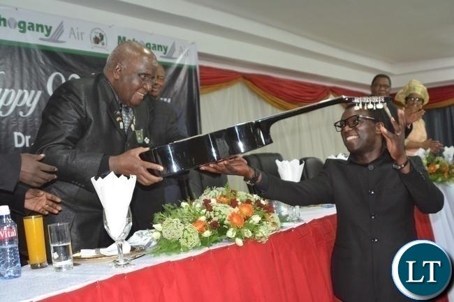 Zambia Association of Musician President Njoya Tembo(r) presents a guitar to First Republican President Kenneth Kaunda(l) during Zambia Association of Musician KK's Birthday Bash in Chongwe