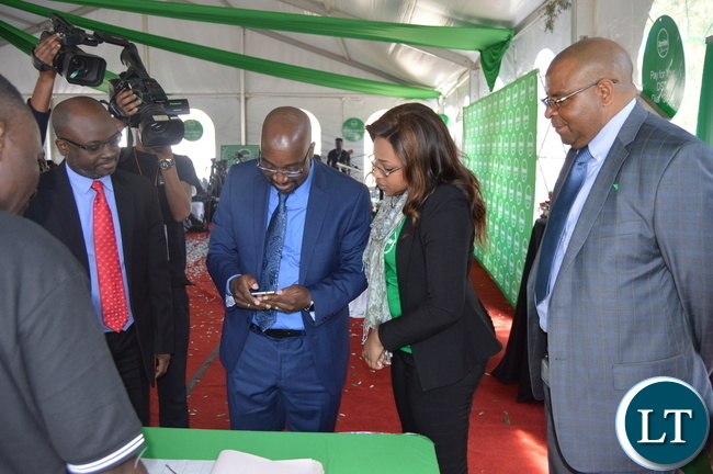 A ZAMTEL staffer performs a demonstration of how ZAMTEL Kwacha works to Transport and Communications Minister Brian Mushimba