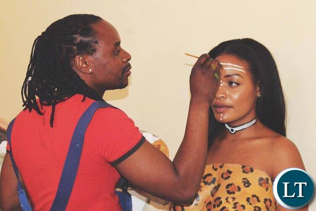 Artist Caleb Chisha working on Iris Kaingu's body art