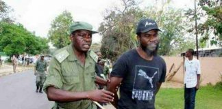 Pilato being led away from the protest scene after being arrested