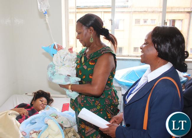 Commerce Minister Margaret Mwanakatwe admiring baby Emmanuel Mwansa baby first born of Lusaka West barracks resident 22 years old Olipah Lungu (laying down) while looking on is UTH Principle Nursing Officer Beatrice Mundia.