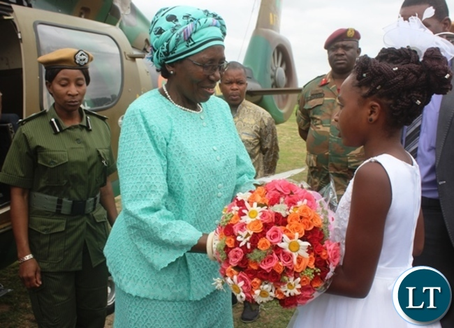 Vice President Inonge Wina receives  a bouquet of flowers from six years old Vanessa Kumwenda upon arrival in Kabwe for the official opening of a fertiliser plant Kabwe. Picture by SUNDAY BWALYA/ ZANIS