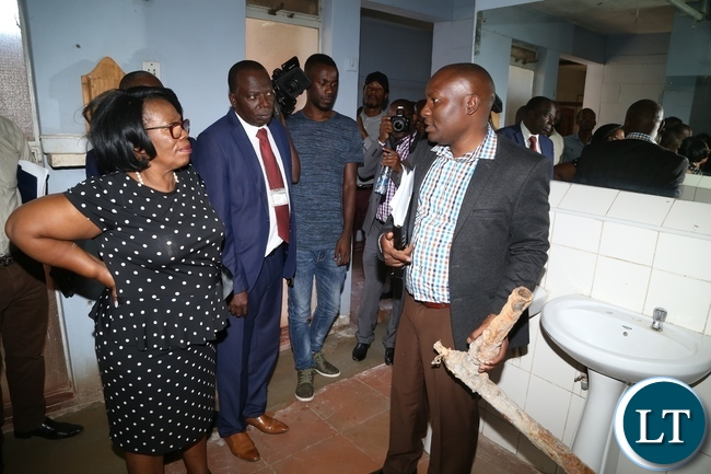 University of Zambia Resident Engineer Ally Nyirenda showing the Minister of High Education Nkandu Luo the part of the water pipes the where removed during the clean up exercise due to cholera at University of Zambia