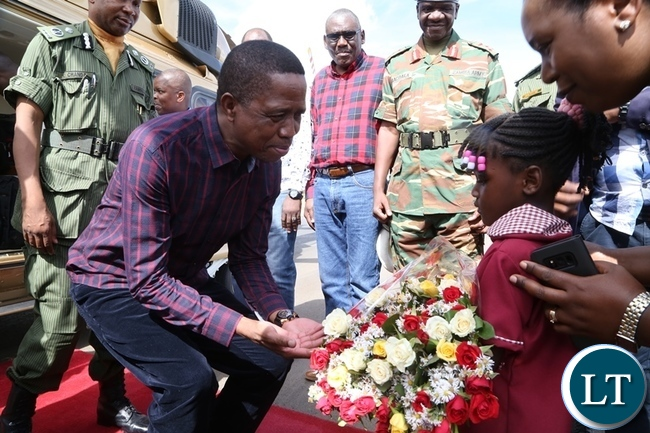 President  Edgar Lungu receive flowers from a 6 years old Jessy band on his arrival at Kakoma Place in Chibomba district of Central Province during his two days working Visit y
