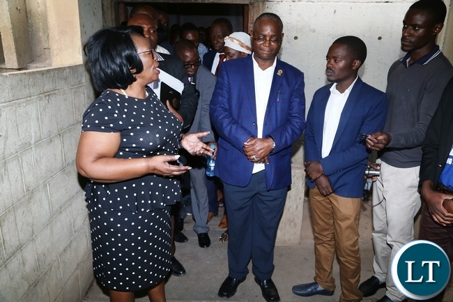 Minister of High Education Prof. Nkandu Luo confers with University of Zambia Vice Chancellor Prof. Luke Mumba during the tour to check on the clean up exercise whilst UNZASU representative Oscar Musukuma looks on