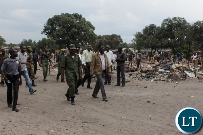 Mongu District Commissioner Susiku Kamona (r) inspecting the demolition exercise and closure of Kaoma-Kaoma Market make-shift structures as a preventive measure against the outbreak of Cholera in Mongu