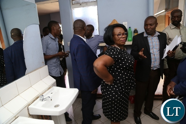 University of Zambia Resident Engineer Ally Nyirenda explaining to Minister of High Education Nkandu Luo the part of the water pipes the where removed during the clean up exercise due to cholera at University of Zambia