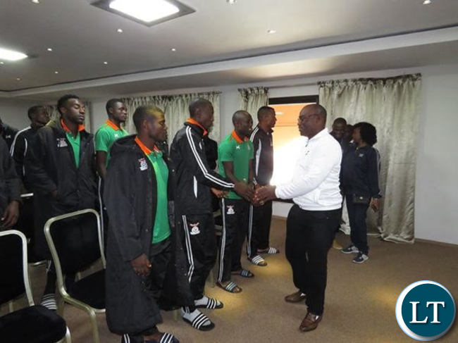 Sports minister Moses Mawere shaking hands with National team Football players