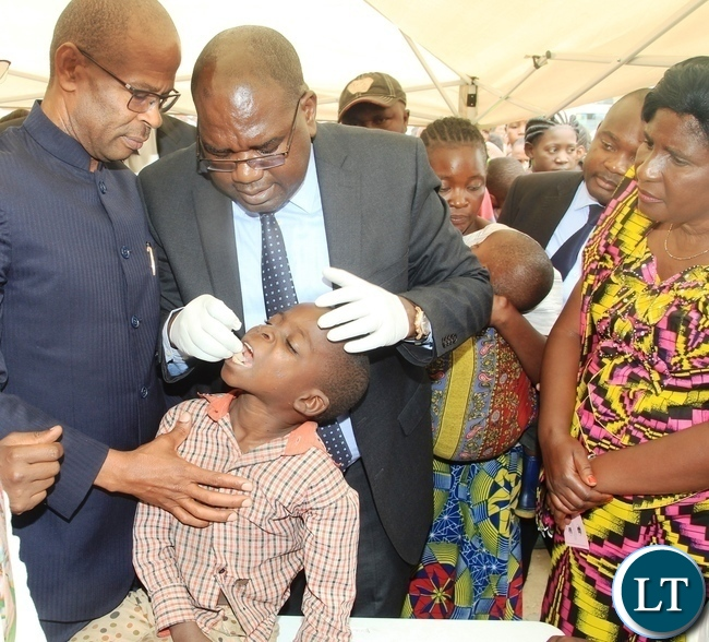 Minister of Health Dr Chitalu Chilufya giving the.oral cholera vaccine to a boy to officially launch the vaccine in Kanyama Mutanda bantu .looking on is area member of parliament Elizabeth Phiri (right) and deputy Secretary to Cabinet Patrick Mvunga (left)