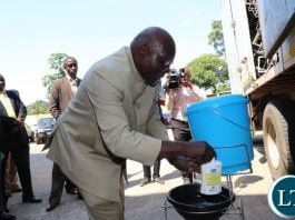 Minister of General Education Dennis Wanchinga hand washing after he flagged off the distribution of water,sanitation and hygiene wash materials in Lusaka