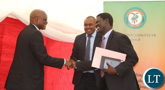 Acting Director General National AIDS Council Fortune Chibamba welcomes Ministry of Health Director Public Health Dr. Andrew Silumesii whilst AIDS Heath Foundation Country Director Dr. Mabvuto Kango during the International Condom Day at Central Mall