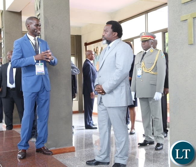 National Heritage Conservation Director Kagosi Mwamulowe explains the point to President Joseph Kabila shortly after laying wreaths at late President Micheal Sata tomb stone during the tour of Presidential burial site in Lusaka