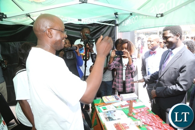 National AIDS Council Worker Lester Nambale stress a point to Ministry of Health Director Public Health Dr. Andrew Silumesii during the International Condom Day tour of stands at Central Mall