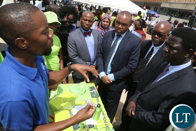 Stand exhibitor explains to Ministry of Health Director Public Health Dr. Andrew Silumesii during the International Condom Day tour of stands at Central Mall
