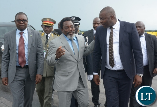 President Joseph Kabila confers with Lusaka Province Minister Bowman Lusambo (r) and Foreign Affairs Minister Joseph Malanji shortly before his departure at Kenneth Kaunda International Airport