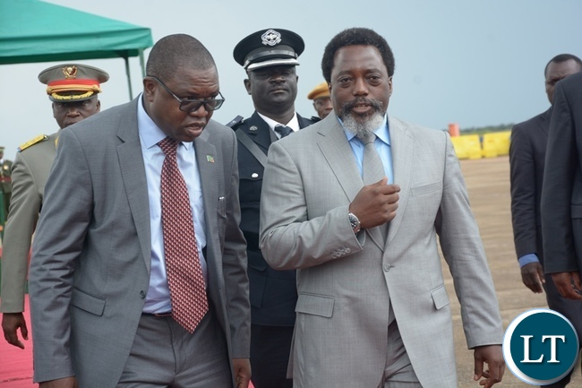 President Joseph Kabila confers Foreign Affairs Minister Joseph Malanji shortly before his departure at Kenneth Kaunda International Airport