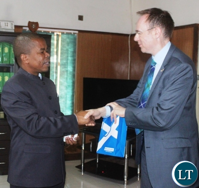 Scottish Minister for international development and Europe Dr  Allasdair Allan presents a gift to Central Province Minister Sydney Mushanga when he paid  a courtesy call on him in Kabwe