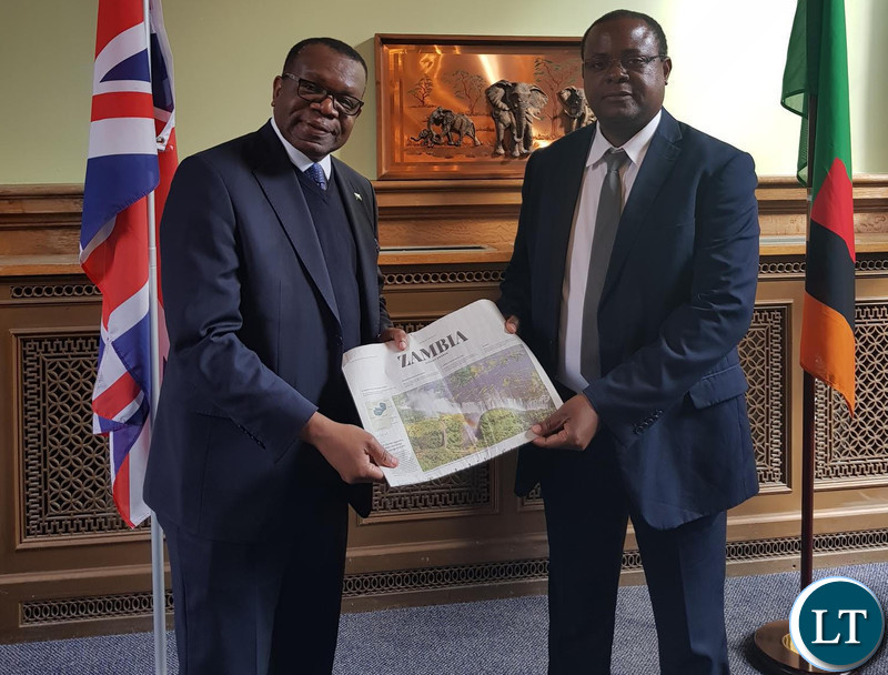 High Commissioner ChiKonde presenting a supplement that appeared in the Daily Telegraph to Dr. Simwinga.