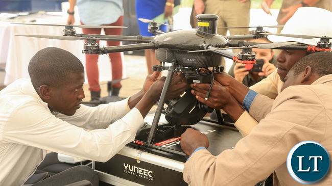 Technicians from SWUAT Technologies prepare a drone to take off.