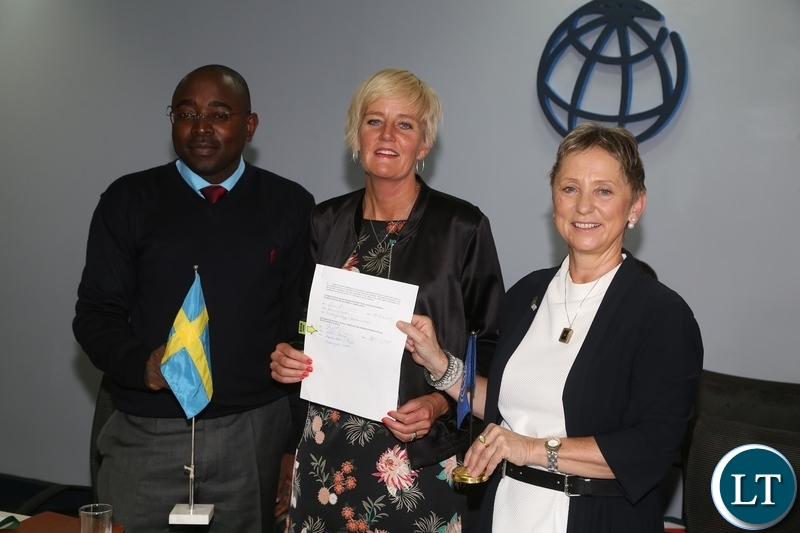 World Bank Country Manager Ian Ruthernberg (r) Swedish Embassy Deputy Head of Mission Karin Svernken and Patrick Mubanga of Rural Electrification Authority showing the Administrative Grant agreement between Government of Sweden and World Bank on Electricity Service Access Project during the signing ceremony