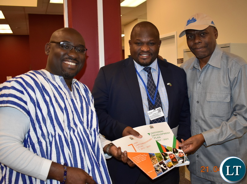 Minister of National Development Planning Alexander Chiteme handing over the Seventh National Development Plan (7NDP) to Voice of America (VOA) veteran broadcast and host of Straight Talk Africa Shaka Ssali and Nightline Africa host Peter Clottey in Washington DC, USA, on Saturday 21 April 2018. PHOTO | CHIBAULA D. SILWAMBA | MNDP
