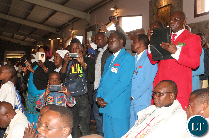 Church goers trying to record the proceedings using their electronic gadgets.