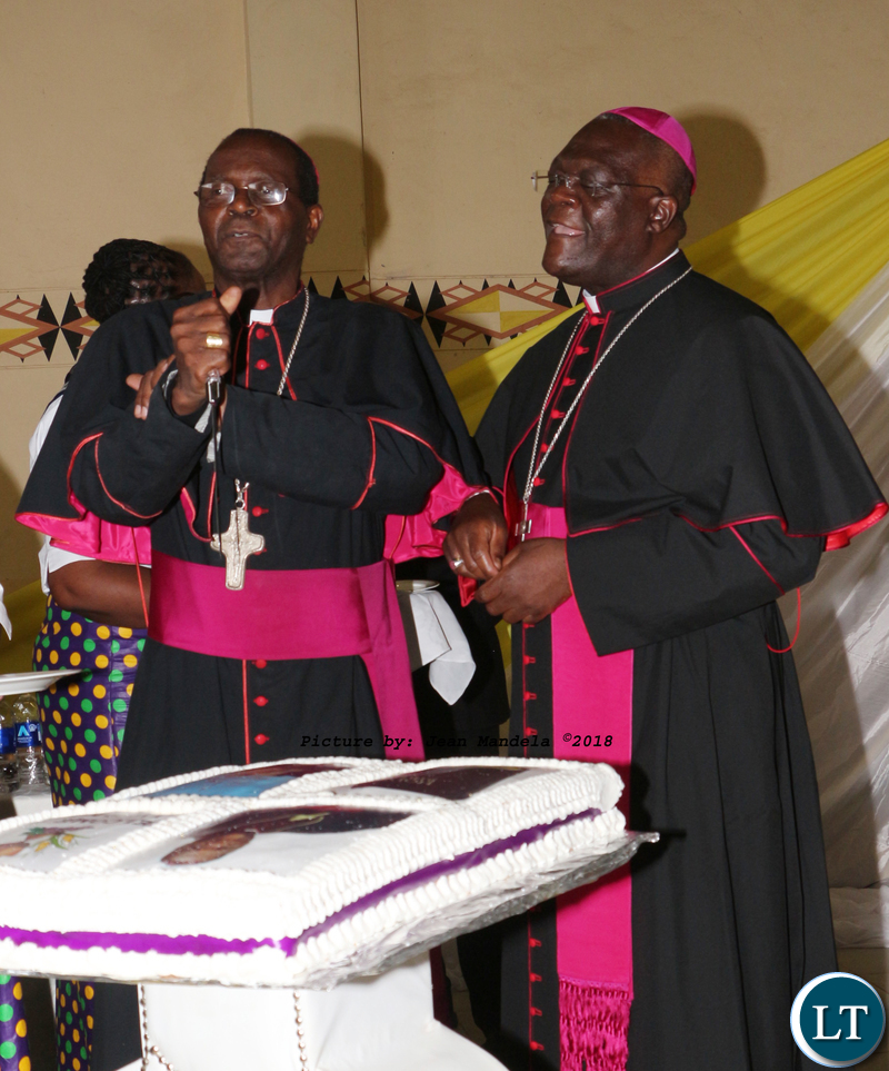 Bishop Telesphore George Mpundu and Bishop Alick Banda cutting a cake.