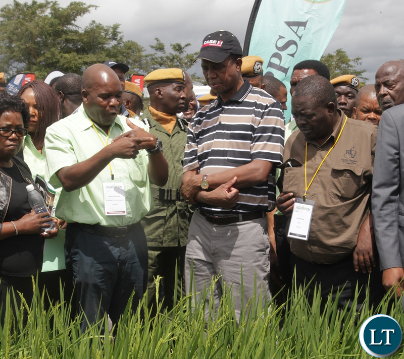 President EdgarLungu listens to an exhbitor on how to grow wheat