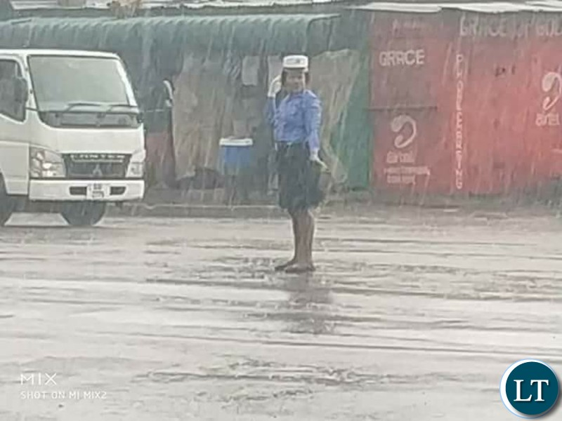Traffic Police Officer Charity Nanyangwe controlling traffic in heavy rains without safety attire and rain coat