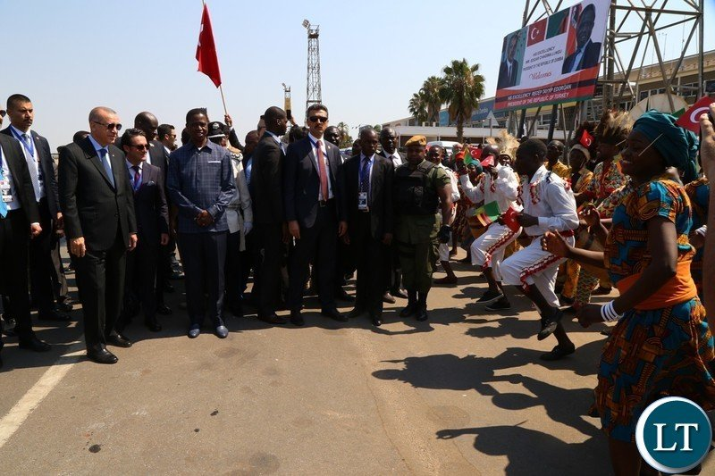 Recep Tayyip Erdogan of the Republic of Turkey and His Excellency, President Edgar Chagwa Lungu being entertained by traditional dancers at Kenneth Kaunda International Airport.