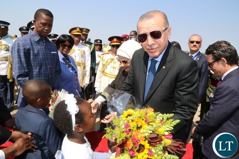 Recep Tayyip Erdogan President of the Republic of Turkey receives a bouquet of f lowers from 7 year old girl Temwani Mponela at Kenneth Kaunda International Airport.