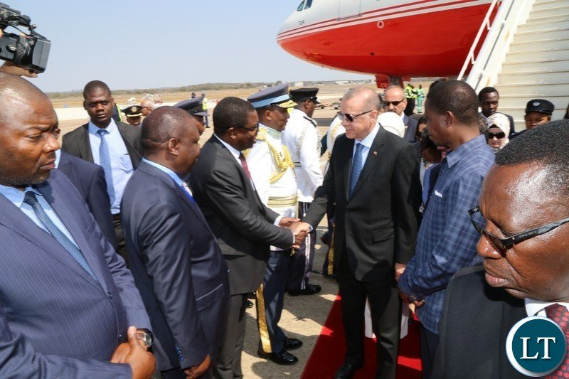 Recep Tayyip Erdogan greets Lusaka Province Minister Bowman lusambo on arrival at Kenneth Kaunda International Airport