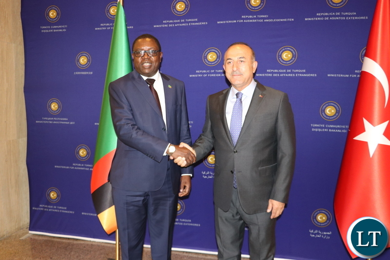 Turkish Minister of Foreign Affairs Mevlut Cavusoglu presents a gift to his Zambian counterpart Joseph Malanji in Ankara