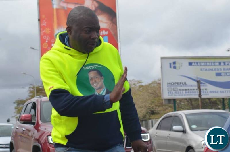 Lusaka Province Minister Bowman Lusambo waves to motorists along the Great East Road as he campaigns for Miles Sampa