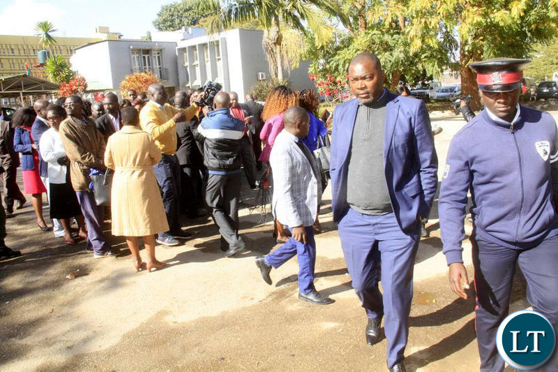 Mr Lusambo walks away from a group of civil servants who came late for work after chasing them away.