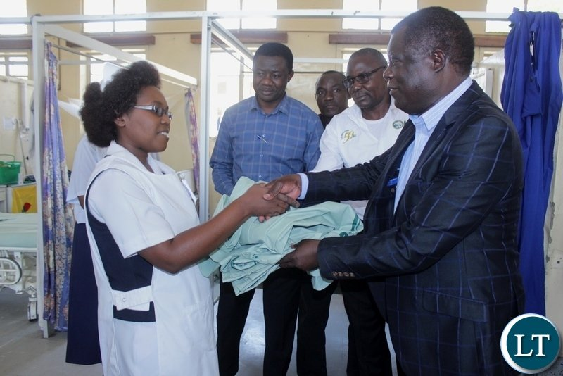 Mongu District Commissioner Susiku Kamona (r) hands over linen to Nurse in-Charge Female Ward Christine Mwendabai (l) as ZSIC-LIFE Regional Manager Arnold Mbangu (2nd r) and Dr. Bimu Yakilembe (2nd l) look on during the donation of 40 linen to Lewanika General Hospital by ZSIC-LIFE to celebrate 50 years, in Mongu