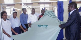 Mongu District Commissioner Susiku Kamona (r) with hospital officials and ZSIC-LIFE official displays a linen during the donation of 40 linen to Lewanika General Hospital by ZSIC-LIFE to celebrate 50 years