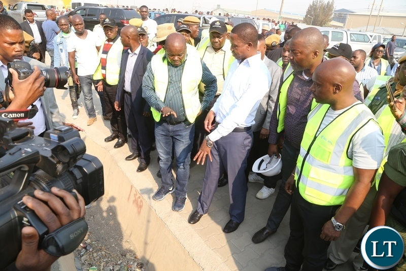 Minister of Infrastructure Ronald Chitotela explains on the progress of the road to President Edgar Lungu during the  inspecting the progress on Lumumba roads