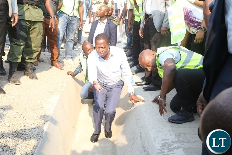 President Edgar Lungu flanked by Minister of Infrastructure Ronald Chitotela (l) and Special Assistant to the President Andrew Chellah (r) inspecting the drainage on Mungwi roads