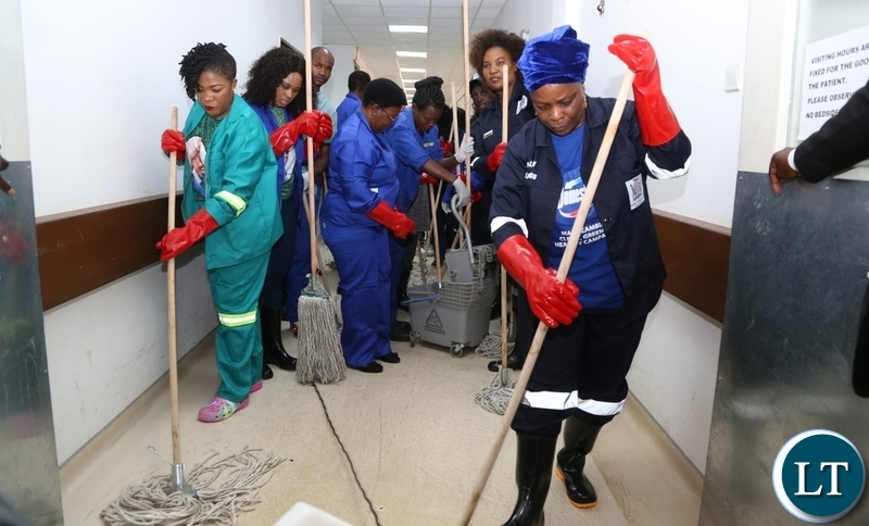 First Lady Esther Lungu (r) with Wife to Lusaka Province Minister Bowman Lusambo Mrs Nancy Lusambo (l) cleaning at University Teaching Hospital (UTH) emergency ward during the keep Zambia Clean, Green and Healthy Campaign