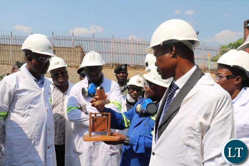 Copperbelt Minister Japhen Mwakalombe listens to Jonathan Manda Manager - Electrowinning - Nchanga Tailings Leach Plant
