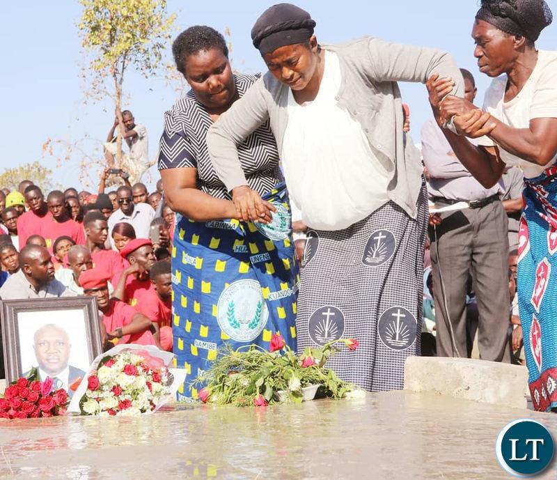 Late Mangango MP Naluwa Mweene's widow helped as he lays wreaths on the grave