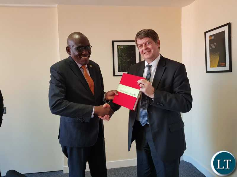 UK's National History Museum Director Sir Michael Dixion presenting a book to Tourism Minister Charles Banda at the Natural History Museum in London.