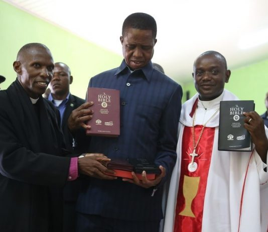President Edgar Lungu receives some bibles from Bishop Sydney Sichilima (left) and Reverend Serge Changa during a church service at UCZ Lilayi