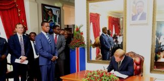 President Edgar Lungu looks on whilst Prince Harry the Duke of Sussex signs in the visitors book at State House shortly after the Prince called on the President