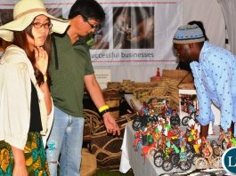 Chrisphin Siamubanga an Artisan shows the tourists art work during the Zambian Artisan Awards in Lusaka.