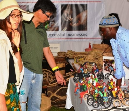 Chrisphin Siamubanga an Artisan shows the tourists art work during the Zambian Artisan Awards in Lusaka.