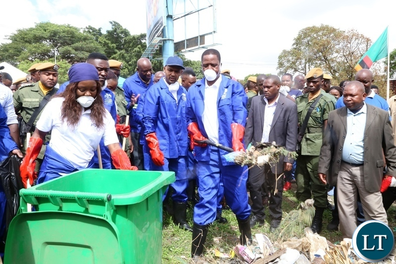 President Edgar Lungu cleaning during the Cavendish University Keep Zambia Clean, Health and Green at Kafue Roundabout
