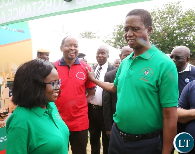 President Edgar Lungu having the light moment with African Parliamentarian Network Against Corruption Zambia Chapter Chairperson Cornelius Mweetwa whilst Deputy Commissioner General Anti-Corruption Commission Rosemary Nkonde looks on during the tour of stands at the commemoration of 2018 International Anti-Corruption Day at Show grounds